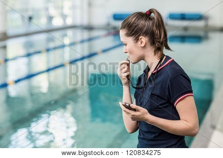 Fit woman blowing whistle at the pool