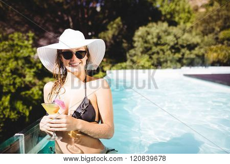 Smiling woman holding cocktail and looking at the camera