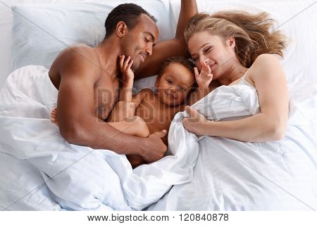 Happy little boy in bed with his parents.