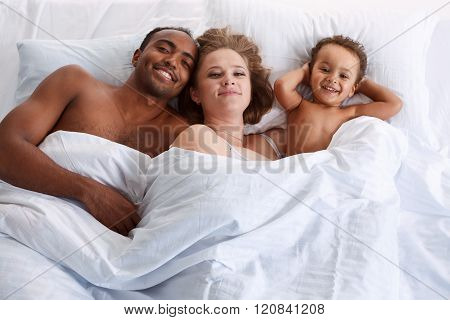 Happy family on white bed in the bedroom.