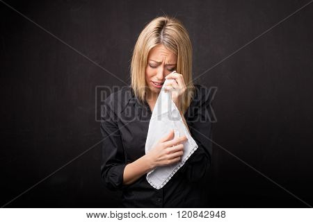 Woman using tissue to wipe her tears