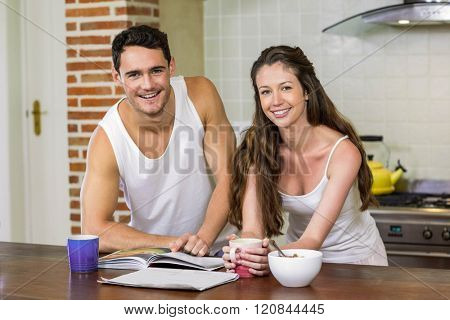 Portrait of young couple standing near worktop and checking their personal organizer in morning