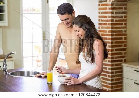 Young couple standing near kitchen worktop and having breakfast together
