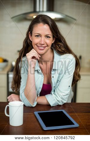Portrait of young woman in kitchen with coffee mug and digital tablet on worktop