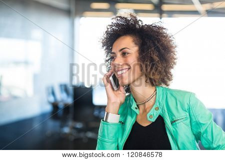 Close-up of young woman talking on mobile phone in front of conference room in the office