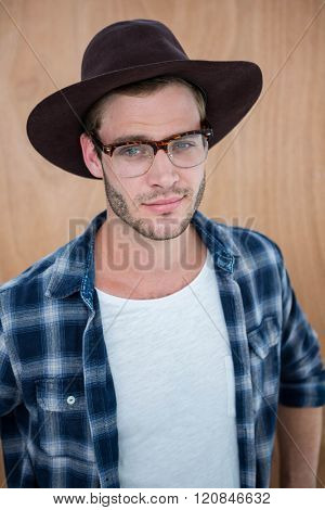 Handsome hipster wearing nerd glasses and hat on wooden background