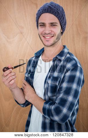 Handsome hipster smocking a pipe on a wooden background