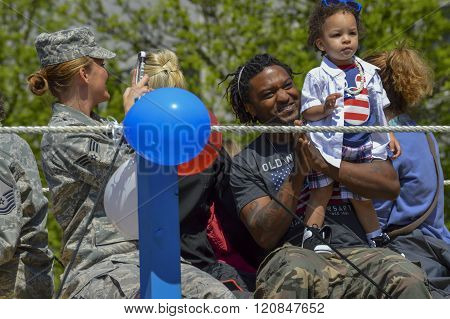 Bangor, Maine/USA-May 26: A military serviceman's baby rides with him upon a flatbed at the Memorial Day Parade on May 26, 2014 in Bangor, Maine. A comrade takes a picture of the moment.