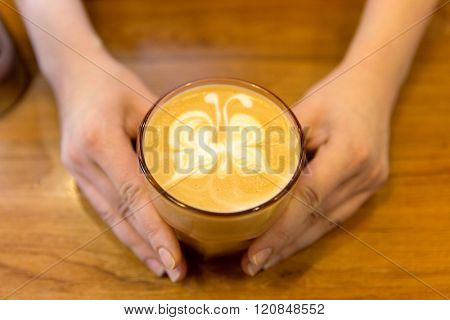 equipment, coffee shop, people and technology concept - close up of hands with latte art etching in coffee cup