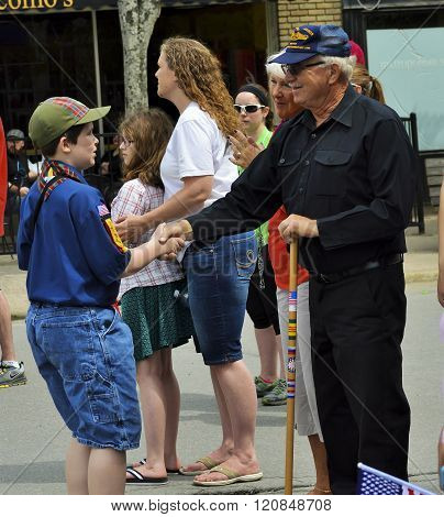 Bangor, Maine/USA-May 25: A uniformed boy scout takes a moment to leave his pack at a parade to shake the hand of a senior military veteran who was watching from the sidelines at the Memorial Day Parade on May 25, 2015 in Bangor, Maine.