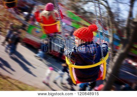 Kids, Having Fun On A Swing Chain Carousel Ride