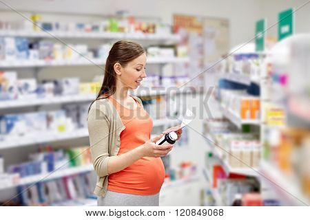 pregnancy, medicine, pharmaceutics, health care and people concept - happy pregnant woman with medication reading prescription paper at pharmacy