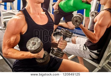 Group of unrecognizable men working on simulator his body at gym.