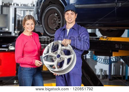 Happy Mechanic And Customer With Hubcap