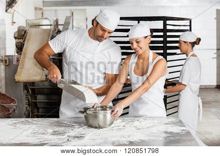 Male And Female Baker's Working Together In Bakery