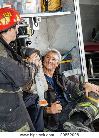 Firefighter Discussing With Colleague On Truck