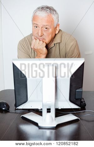 Serious Senior Man Sitting At Computer Desk In Class