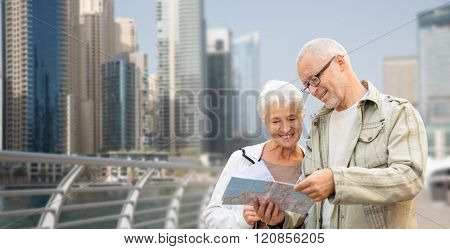 family, age, tourism, travel and people concept - happy senior couple with map and city guide on street over dubai city waterfront background