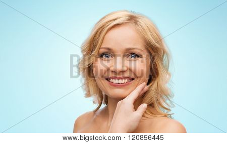 beauty, people and skincare concept - smiling woman with bare shoulders touching face over blue background