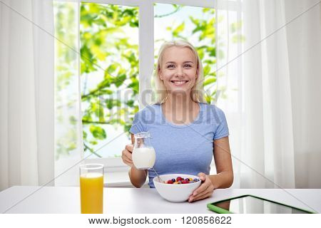 healthy eating, diet, lifestyle and people concept - smiling young woman with milk and cornflakes having breakfast over green natural background