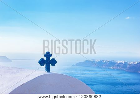 Blue cross on the church roof in Fira on Santorini island, Greece. Caldera view, Aegean sea.