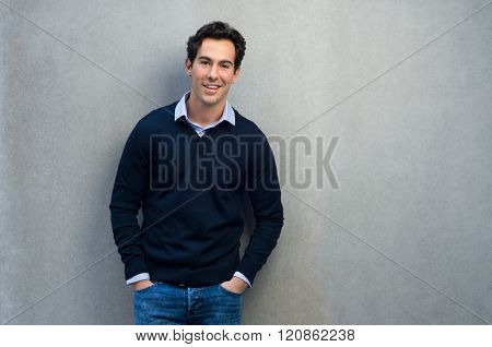 Happy man leaning on a grey wall. Handsome young man in casual leaning against a grey background and copy space. Young businessman looking at camera with hands in pocket.