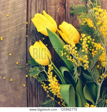 Spring flowers: yellow tulips, mimosa on the old wood background. Toned image.