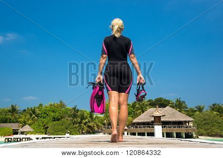 Woman Holding Mask And Flippers For Swimming On Wooden Pier