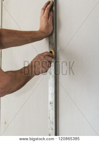 Cutting gypsum board with a knife. Construction and installation work on plasterboard walls.
