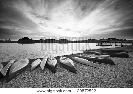 Line Up Of Canoes At The Lakeside Facing Sunset In Black And White