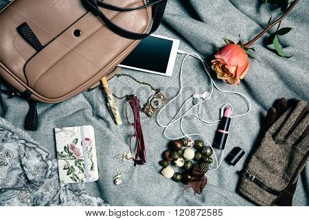 Feminine accessories from handbag over grey background