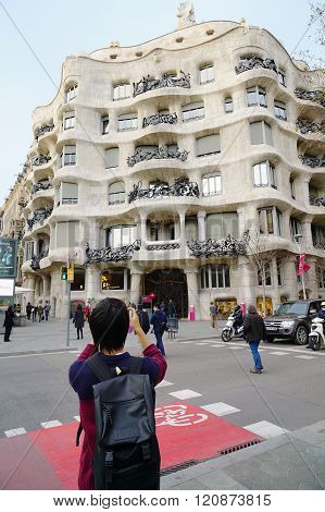 tourist taking picture of Gaudi building Casa Mila La Pedrera in Barcelona