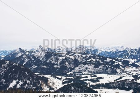 Widespread mountain range covered with evergreen forests and patches of thick snow under overcast skies