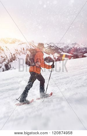 Side view of cross country snowshoe trekker with poles climbing uphill in winter snow storm with beautiful mountains in background