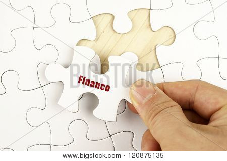 Finance Concept. Hand Holding Piece Of Jigsaw Puzzle Showing Finance Word.