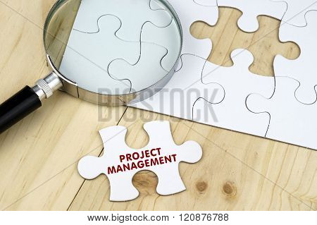 Magnifying glass with jigsaw puzzle on wooden surface
