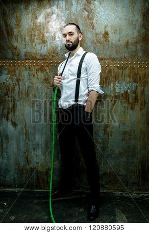 Handsome man posing in white shirt smoking hookah
