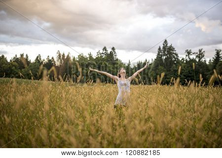 Young Woman Enjoying Life In Beautiful Nature Standing With Her Arms Outstretched