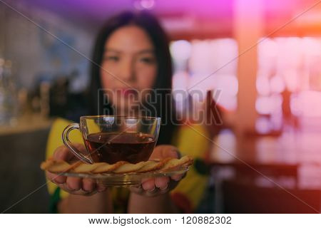 Woman In Colorful Dress Is Drinking And Sipping Hot Tea In Coffee Shop, Blurry Woman And Filtered Ef