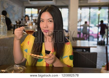 Woman in colorful dress is drinking and sipping hot tea in coffee shop/ Woman is drinking hot tea