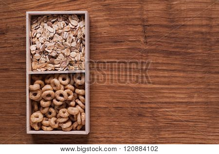 Cereals And Oat Flakes In Wooden Box On Brown Wooden Table - Top View