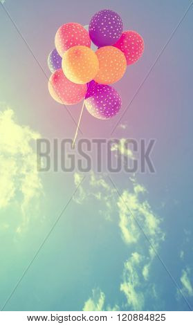 Vintage photo of colorful balloons on blue sky. Concept of love in summer, valentine, wedding and honeymoon
