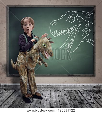 Surprised boy dressed in fancy dress as a dinosaur with chalk tyrannosaurus rex on blackboard concept for education, history, science and imagination