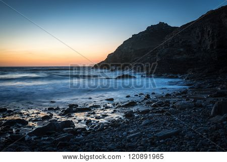 Long exposure of waves lapping the stony shore at sunset, St. Agnes, Cornwall, UK