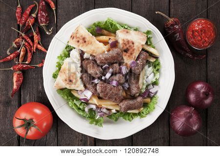 Cevapcici, bosnian minced meat kebab with somun bread, onion and french fries