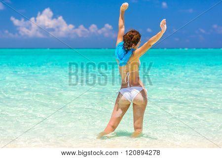 Young woman in bikini standing in the water on beautiful maldivian beach