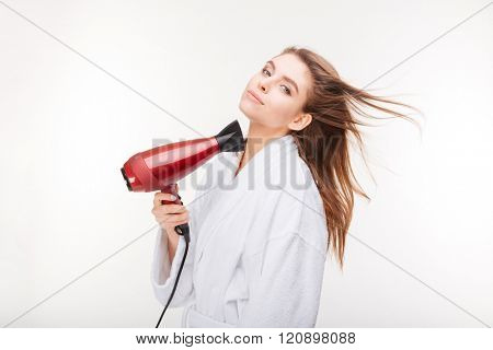Beautiful sensual young woman in bathrobe  drying her hair with dryer over white background