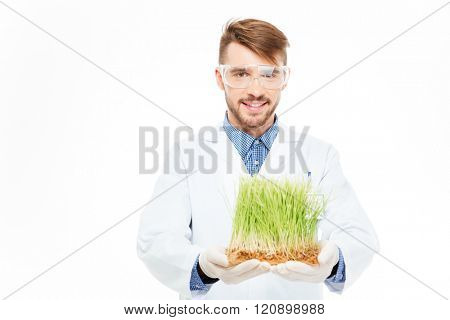 Happy male engineer showing a modified plants isolated on a white background