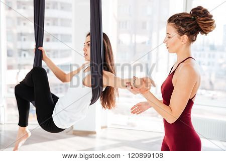 Serious young woman trainer teaching beautiful girl doing aerial yoga in studio