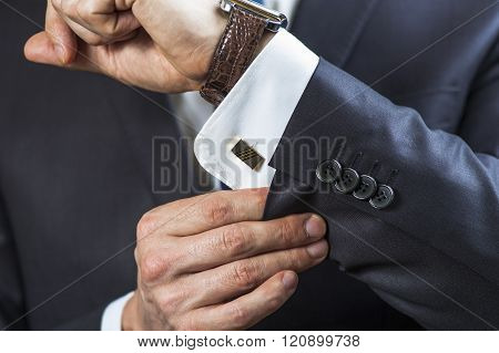 Elegant man correcting his cufflinks and sleeve.
